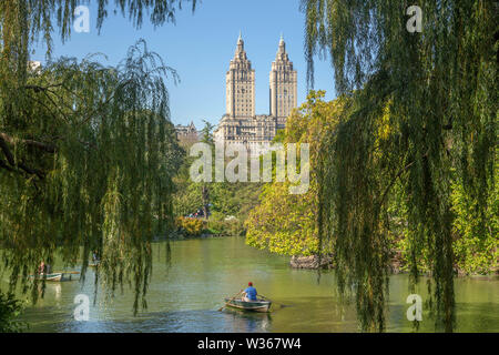 New York City, NY, USA - October 15, 2013: rowing a boat at Central Park lake, in the middle of trees and buildings as background. - Stock Photo