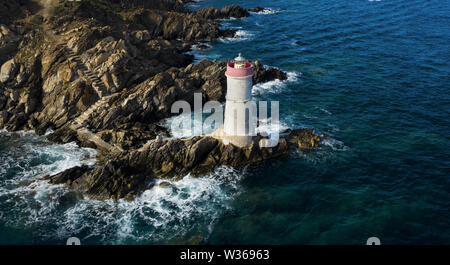 View from above, stunning aerial view of an old and beautiful lighthouse located on a rocky coast bathed by a rough sea. Faro di Capo Ferro. - Stock Photo