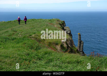 Two Woman Walking near the Chimney Tops on the Giant's Causeway Coastal Path, County Antrim, Northern Ireland, UK - Stock Photo