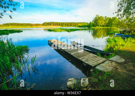Fishing pier on the river a picturesque landscape with a boat. Summer - Stock Photo