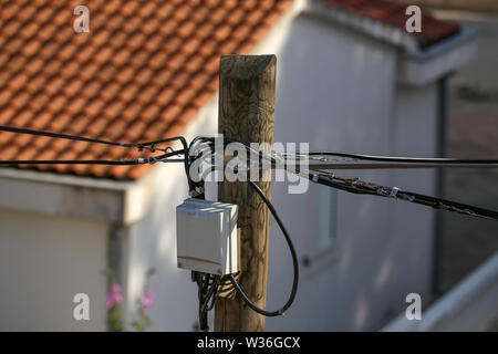 Distribution box on a high wooden power pole. - Stock Photo