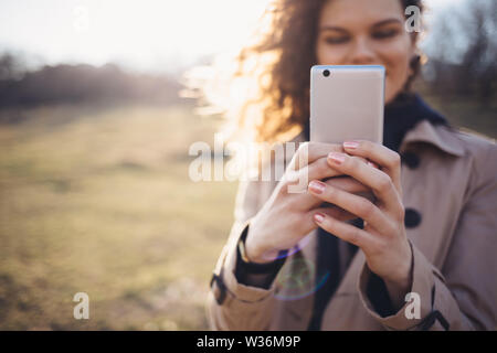 Happy young woman wearing beige coat holding smart phone uses it standing outdoors in autumn field, sun shines through her hair. - Stock Photo