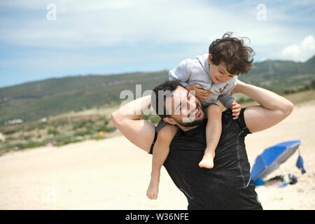 father playing with son in Bolonia beach - Stock Photo