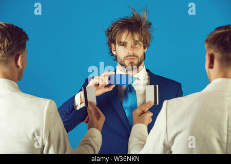 Men wearing white jackets, back view. Information and cooperation. Business ethics concept. Businessmen exchanging cards on blue background. Group of - Stock Photo