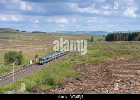 First Transpennine Express class 350 electric train passing Shap Wells on the west coast mainline in Cumbria with a Manchester Airport to Glasgow train - Stock Photo