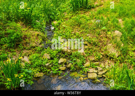 tiny water fall surrounded by rocks and plants in a beautiful garden, nature background - Stock Photo