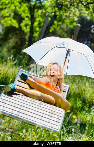 Attractive female person legs in heels lying on deckchair deck-chair in Green forest natural environment nature laughing loudly looking at camera MR - Stock Photo