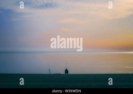 Lone fisherman on beach in the early morning. - Stock Photo