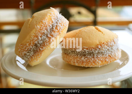 Pair of Alfajores, Traditional Latin American Sweetened Milk Filling Cookies Served on White Plate - Stock Photo