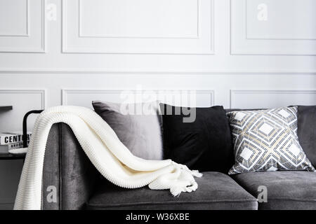 Living room interior with with gray fablic sofa, comfy pillows, plaid and knitting whithe blanket. Decoration modern  room interior design. - Stock Photo