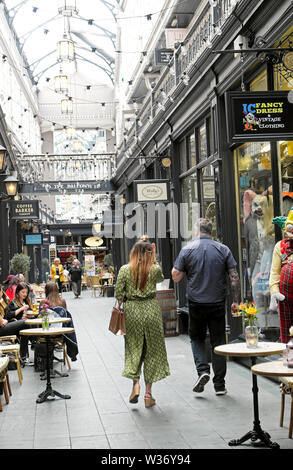 People shoppers walking , sitting, eating, drinking coffee in Castle Arcade covered shopping area in Cardiff Wales UK  KATHY DEWITT - Stock Photo