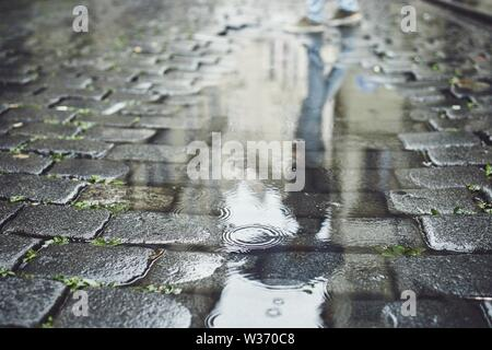 Reflection in puddle. Man with umbrella walking on cobblestone street in rain. Prague, Czech Republic. - Stock Photo