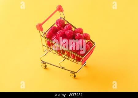 ripe raspberries in shopping cart on orange background, concept buying sweet berries