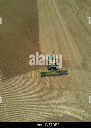 Aerial of combine harvester harvesting wheat in large paddock Eyre Peninsula South Australia - Stock Photo