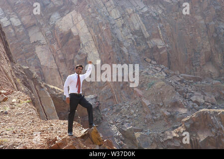 Businessman standing with his hand raised - Stock Photo