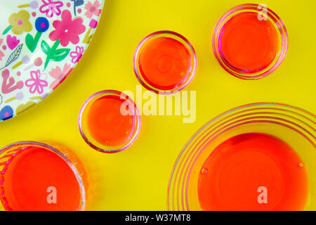 Red fruit juice in glass bowls and brightly colored plate on yellow background - Stock Photo