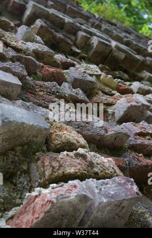 Old damaged brick-wall of german bunker in forests - Stock Photo