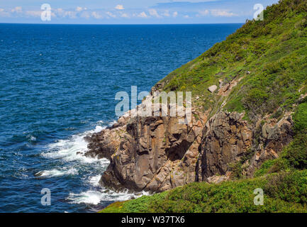 09 July 2019, Denmark, Helligpeder: Steep cliffs on the west coast of the Danish Baltic Sea island near the small fishing village of Helligpeder. The island Bornholm is, together with the offshore archipelago Ertholmene, Denmark's most eastern island. Thanks to its location, the island of Bornholm counts many hours of sunshine. Photo: Patrick Pleul/dpa-Zentralbild/ZB - Stock Photo