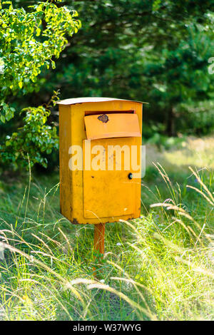 old rusty yellow mailbox on green lawn, trees in background - Stock Photo