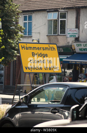 viewed across queueing traffic, hammersmith bridge closed to vehicular traffic sign on the south circular in southwest london, england - Stock Photo
