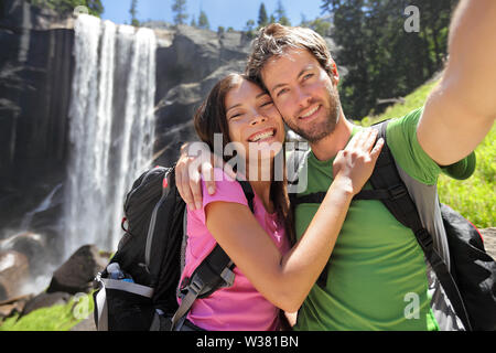 Selfie couple hikers at Yosemite National Park taking a self portrait picture with beautiful waterfall, Vernal Fall. Young hiking couple relaxing after hike in beautiful summer nature landscape. - Stock Photo