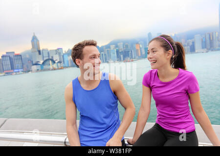 Runners relaxing after workout in Hong Kong city. Running caucasian and asian man and woman post run taking a break talking together on the Avenue of the Stars in Victoria harbor, HongKong Skyline. - Stock Photo
