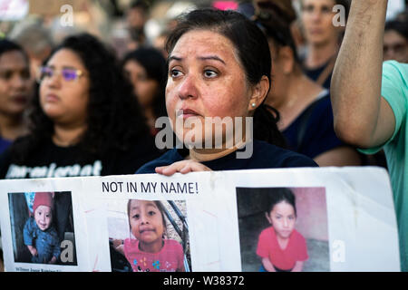 A woman holds a placard with photos of migrant children who have died while in Border Patrol custody, as people protest against ICE raids and migrant detention camps during a vigil outside an Immigration and Customs Enforcement detention center in Los Angeles. Organizers called on the Trump administration to close all migrant detention camps. Similar Lights for Liberty rallies and vigils took place across the nation. - Stock Photo