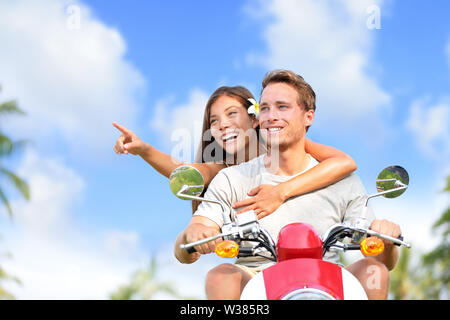 Happy couple pointing on scooter travel vacation. Young Asian woman showing her boyfriend a location while driving a moped on a road trip during summer holidays with blue sky and clouds background. - Stock Photo
