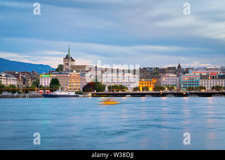 Shuttle boat on Lake Geneva and the view of downtown of Geneva. St.Peter cathedral and Mont Saleve in the background. - Stock Photo