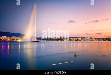 Beautiful sunset on Geneva Lake. View of the famous fountain, called Jet'Eau and the downtown of Geneva - Stock Photo