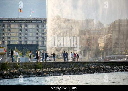 Tourists walking on the pier which leads to the water jet, called Jet d'Eau. Geneva. Switzerland - Stock Photo