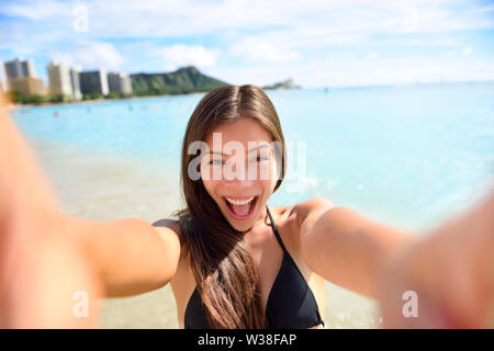 Selfie fun woman taking picture at beach vacation. Summer holiday girl happy at smartphone camera taking self-portrait on her Hawaiian travel vacations in Waikiki, Honolulu city, Oahu, Hawaii, USA. - Stock Photo