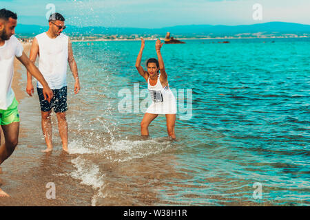 Group of young multiethnic friends women and men at the beach in summertime spraying with sea - Stock Photo