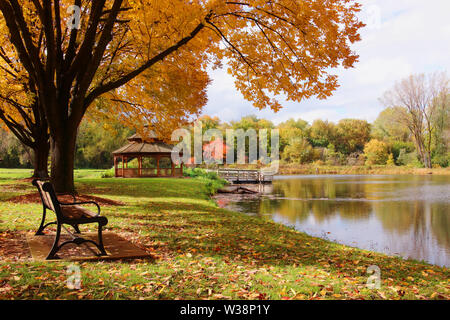 Beautiful autumn landscape with colorful trees around the pond and wooden gazebo in a city park. Lakeview park, Middleton, Madison area, WI, USA. - Stock Photo