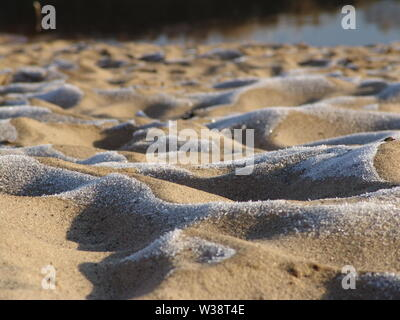 Sand in the hoarfrost on the river bank