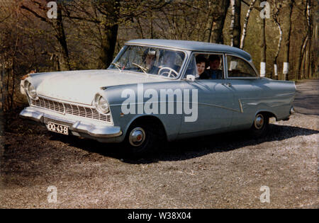 1960, historical, people sitting in a Ford Taunus P2 (17M) motor car parked beside some woodland. Similar to the UK's Ford Cortina. the Taunus was made by Ford Germany and sold throughout Europe. The stylish  car was named after the Taunus mountain range in Germany and was the second newly-designed German Ford to be launched after the war. - Stock Photo
