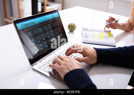 Close-up Of A Businessperson's Hand Using Laptop With Calendar Over White Desk Stock Photo