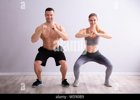 Side View Of Happy Fitness Couple In Sportswear Doing Squat Exercises At Gym - Stock Photo