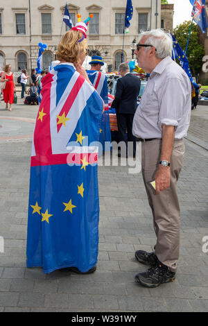 Westminster, London, UK. 26th June, 2019. A Brexit Remain campaigner wears a Union Jack and EU flag as she chats to a man outside the House of Commons. Credit: Maureen McLean/Alamy - Stock Photo
