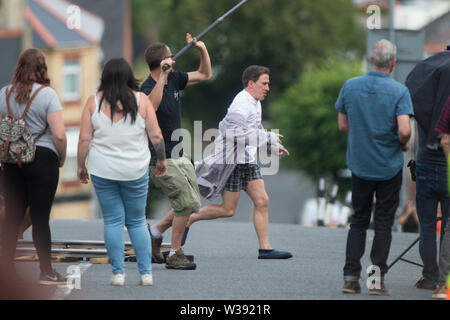 Barry, UK. 13th July, 2019. 'Uncle Bryn' played by Rob Bryden films a scene for the BBC comedy Gavin & Stacey Christmas special in Trinity Street, Barry, South Wales. Credit: Mark Lewis/Alamy Live News - Stock Photo