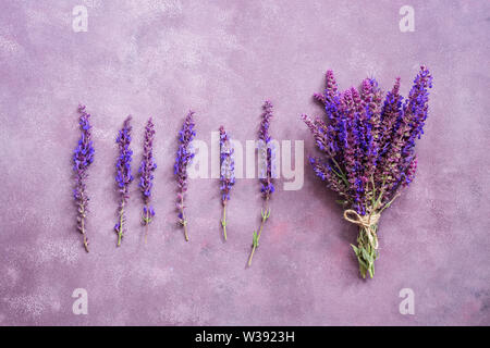 Flower arrangement and a bouquet of purple flowers on a beautiful background. View from above, flat lay - Stock Photo