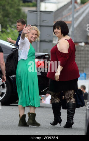 Barry, UK. 13th July, 2019. (L-R) Joanna Page who plays 'Stacey' and co-writer Ruth Jones who plays 'Nesa' wave to onlookers during a break in filming of the BBC comedy Gavin & Stacey in Trinity Street, Barry, South Wales. Credit: Mark Lewis/Alamy Live News - Stock Photo