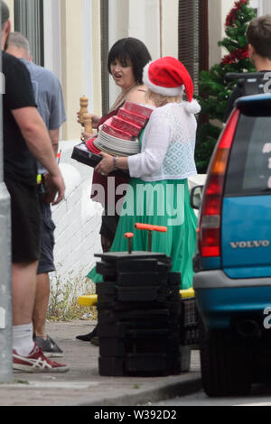 Barry, UK. 13th July, 2019.  Co-writer Ruth Jones who plays 'Nesa' and Joanna Page who plays 'Stacey' rehearse a scene during filming of the BBC comedy Gavin & Stacey Christmas special in Trinity Street, Barry, South Wales. Credit: Mark Lewis/Alamy Live News - Stock Photo