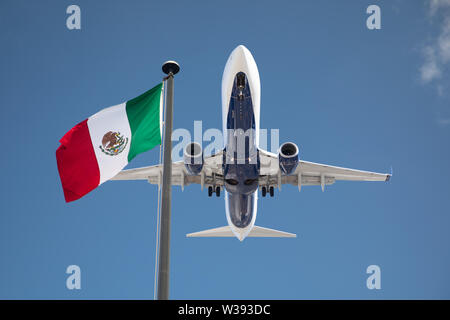 Bottom View of Passenger Airplane Flying Over Waving Mexico Flag On Pole. - Stock Photo