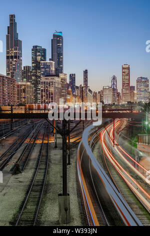 Commuter trains light up the tracks near Soldier Field below the beautiful skyline of downtown Chicago, Illinois, on a clear summer night. - Stock Photo