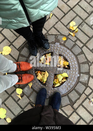 Luke with the inscription Sewerage of Leningrad. Top view of the pavement tile with autumn leaves. Feet in the shoes of two women and one man. St. Pet - Stock Photo