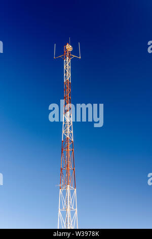 Red and white mobile phone cell tower repeater, with a small microwave dish. - Stock Photo