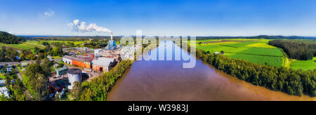 Broadwater sugar mill on banks of Richmond river across sugarcane farmed fields and planes in aerial wide panoramic view. - Stock Photo