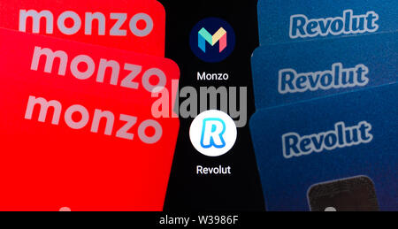 Macro photo of Monzo and Revolut bank cards on the smartphone screen next to their apps. Conceptual photo to highlight the competition. - Stock Photo