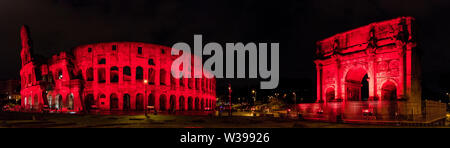 The Colosseum and Arch of Constantine lit red for persecuted Christians in Rome, Italy - Stock Photo